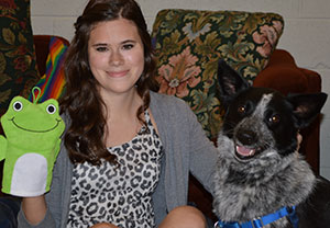 Student holding a puppet next to a therapy dog