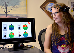 Student looking at her brain activity with an EEG device